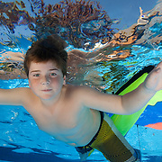 boy swimming underwater flying his kite