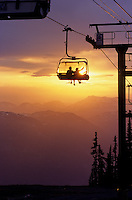 Couple ride the chairlift, summer sunset