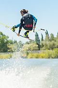 Male athlete jumping while wake boarding on the Snake River in Burley, Idaho.