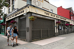© Licensed to London News Pictures. 20/06/2020. London, UK. A couple walk past 'The Old Ale Emporium' pub on Green Lanes, Haringey, north London. Pubs, restaurants and cafes will  reopen on 4 July. The Old Ale Emporium' pub has been closed since 23 March following the coronavirus lockdown. The government has lowered COVID-19 alert level from four to three raising expectations that 2 meter distancing restrictions could be cut. Photo credit: Dinendra Haria/LNP