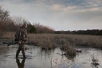 MOSSBERG SHOTGUN HUNTER WEARING REALTREE AP CAMOUFLAGE WALKING THROUGH WETLAND