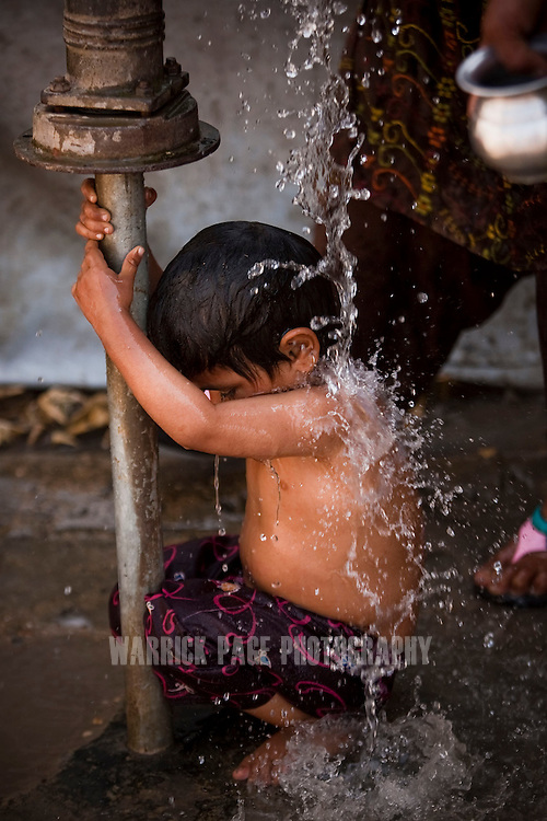 A child is bathed at a water-well at an IDP camp for the flood-affected, on 22 February, 2011, in Larkana, Pakistan. Extreme poverty, poor diet and health, exposure to disease, and inadequate sanitation and hygiene annually produce alarming levels of malnutrition amongst children, but the floods of 2010 and 2011 have increasingly endangered an already vulnerable population. Child malnutrition has breached emergency levels in Pakistan - particularly Sindh province - after monsoon floods devastated the country's poorest region for a second year. Malnourishment It is the single biggest contributor to under-five mortality, increasing the risk of infections and slowing recovery from illness. It stuns both mental and physical growth and their future capacity, sapping the next generation's ability to meet the demands of a country already facing an unstable future. According to UN reports, hundreds of thousands of children in Pakistan suffer from severe-acute-malnutrition, with 15.1% of children experiencing acute malnourishment. The Economist recently reported that 44% of children in Pakistan suffer from varying degrees of malnutrition. (Photo by Warrick Page)