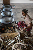 Palm sugar being manufactured in a small shelter on the side of the road in Burma.