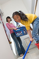Woman and girl (10-12) doing housework