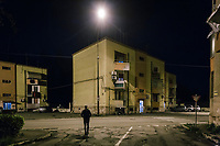 TARANTO, ITALY - 22 FEBRUARY 2018: A man walks by a residential building in Tamburi, the working-class district adjacent the ILVA steel mill in Taranto, Italy, on February 22nd 2018.<br /> <br /> Taranto, a  formerly lovely town on the Ionian Sea has for the last several decades been dominated by the ILVA steel mill, the largest steel plant in Europe. It was built by the government in the 1960s as a means of delivering jobs to the economically depressed south, but has been implicated for a cancer as dioxin and mercury have seeped into local groundwater, tainting the food supply, while poisoning the bay and its once-lucrative mussels.