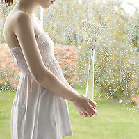 Slender young woman wearing a white dress with pale skin holding a vase with baby's breath flowers, against a window with rain drops on it.