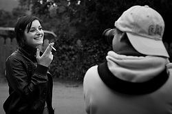 A young woman poses for a photographers while smoking a cigarette Mendocino, California, USA.