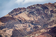 Colorful mountains reveal complex geologic forces above Artists Drive, in Death Valley National Park, California, USA.