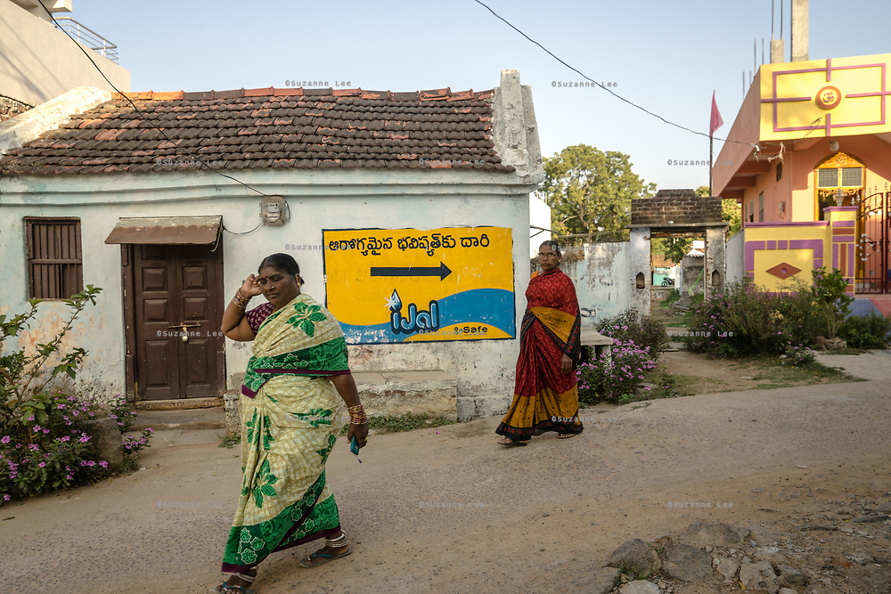 Pedestrians walk past a signage for a Safe Water Network iJal station station in Rangsaipet, in Waragal, Telangana, Indiia, on Saturday, February 9, 2019. Photographer: Suzanne Lee for Safe Water Network