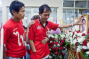 Apr. 15, 2010 - BANGKOK, THAILAND:  A man and his brother at the coffin of their youngest brother, who was killed in Thai street riots Saturday, during a chanting service at Wat Hualamphong in central Bangkok Thursday for the people who died during anti-government street violence Saturday. Another protestor died today, bringing the civilian death toll to 17. Hundreds of people are still hospitalized and many are in intensive care. Officials expect the death toll to increase through the week as people die of their wounds. A date has not been set for the victims' Buddhist funeral rites, but the chanting services will continue on a daily basis until the dead are cremated. Many people believe a violent government crackdown is less likely now since the violence seems to have shocked many Thais, but it has also galvanized protestors who show no sign of backing down.   Photo By Jack Kurtz