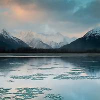 Sunrise starts to color the clouds over snow-capped mountains, reflecting in the river. Haines, Alaska, USA.