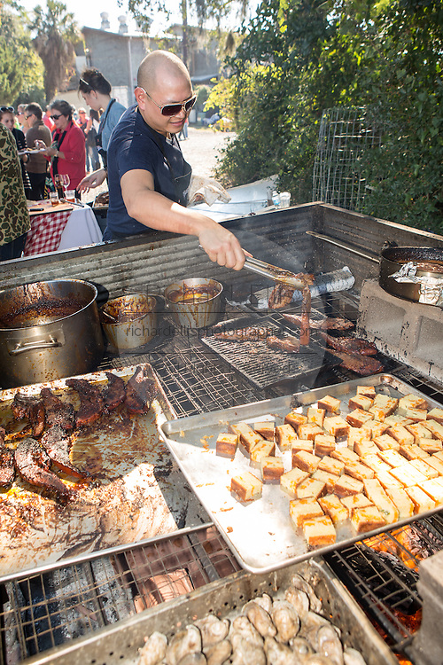 Chef Nick Liu from team Canada prepares BBQ salmon during Cook it Raw outdoor BBQ event on Bowen's Island October 26, 2013 in Charleston, SC.