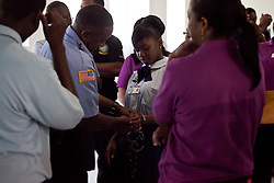 Adia Benjamin, 17, of Charlotte Amalie High School is placed in cuffs by Officer Neville Robinson of the Bureau of Corrections.  Adia who wants to major in law attended the Law Enforcement Career Fair at UVI.