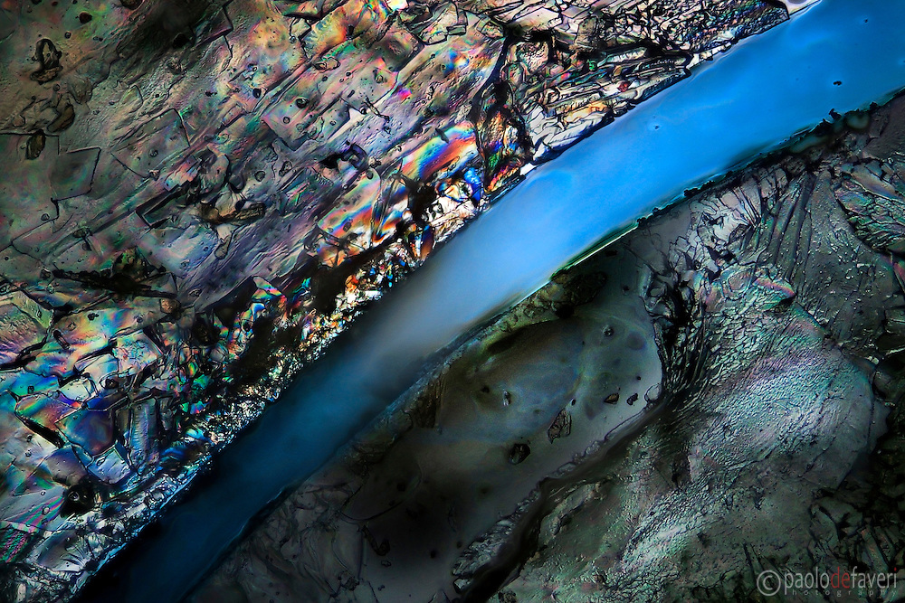 "A view at the microscope of salt and sugar crystals on glass in polarized light. The ""river"" is actually a crack in the mass of sugar and salt, unveiling the glass beneath. A microscopic grand canyon in a colorful desert."