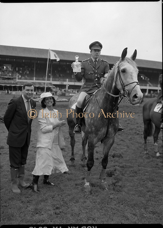 Jameson Whiskey International at the Dublin Horse Show.  (R39).1986..07.08.1986..08.07.1986..7th August 1986..The Jameson Whiskey International at the Dublin Horse Show in the RDS was won by Peter Charles of Great Britain. He rode 'Merrimandias' to victory in the event...Image shows Capt Gerry Mullins with the trophy presented to him by Mrs Marie Cummins, wife o f the Managing Director, Irish Distillers. capt Mullins the Irish Whiskey Classic aboard 'Glendalough'. Mr Michael Cummins also features in the picture. Jameson's, Irish, Whiskey, jameson,