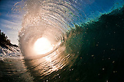 The bright light of the setting sun lights up this powerful wave
