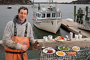 Samuel Tucker, a lobsterman, with his typical day's worth of food in front of his boat at the Great Diamond Island dock in Maine.   (From the book What I Eat: Around the World in 80 Diets.) The caloric value of his day's worth of food in March was 3,800 kcals. He is 50 years of age; 6 feet, 1.5 inches tall; and 179 pounds. Sam works the lobster boat by himself, saving on labor, but in the summertime his son Scout comes along. ?He's a blast,? says Sam. ?I take him and some of his friends out; they're all just leaning over the rail in their life preservers looking to see what's in the trap when it comes up. They're pretty good at saying, 'He's got a keeper.'? Sam's state license restricts his traps to the bay, where he averages only one lobster for every two traps. After paying for fuel and bait, there's not much profit. He supplements his income with fish auction commissions, and his family's diet with venison culled from the island's deer population.  MODEL RELEASED.
