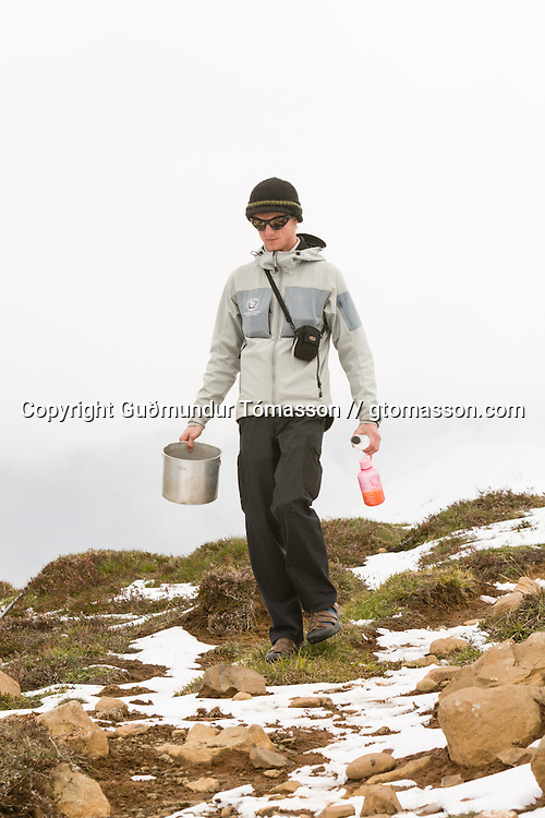 Tourist with a pot and water bottles.