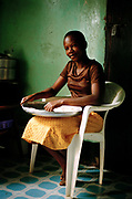 A girl sifts corn flour for ugali, a traditional African meal. Kampala, Uganda.