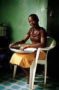 Girl sifts corn flour preparing ugali, a traditional African meal. Kampala, Uganda.
