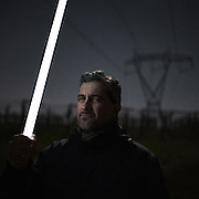 "Orlando Volpe, a member of the ""No Power Line"" committee, holds a neon tube which, because of the Tesla effect, ignites spontaneously under the wires of a power line in the valley of Frentano.<br />