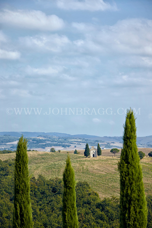 A view through cypress trees of the Val D'Orcia in the Tuscany Region of Italy.