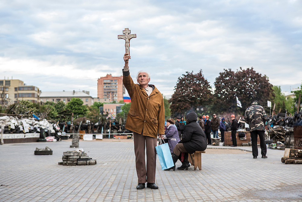 DONETSK, UKRAINE - MAY 8: A man representing a group of Orthodox Christians holds a cross outside the occupied regional administration building, which serves as the local headquarters for pro-Russian activists, on May 8, 2014 in Donetsk, Ukraine. Tensions in Eastern Ukraine are high after pro-Russian activists seized control of at least ten cities and ahead of the Victory Day holiday and a planned referendum on greater autonomy for the region. (Photo by Brendan Hoffman/Getty Images) *** Local Caption ***
