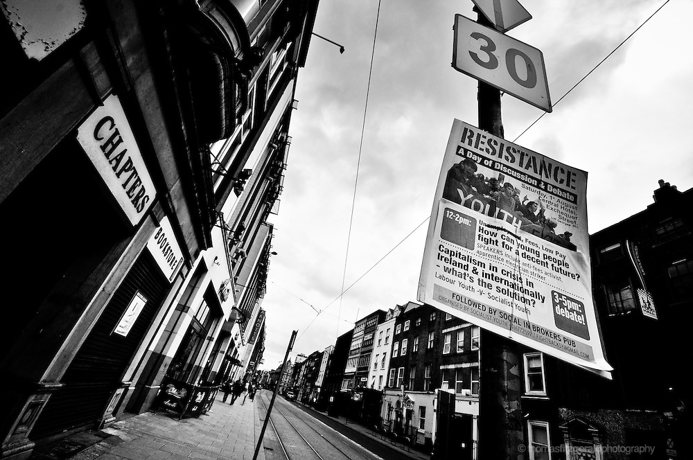 The poster of an activist group hangs on a lamp post outside a book store in Dublin city on a dark and stormy day. Black and White.<br /> For Editorial Use Only
