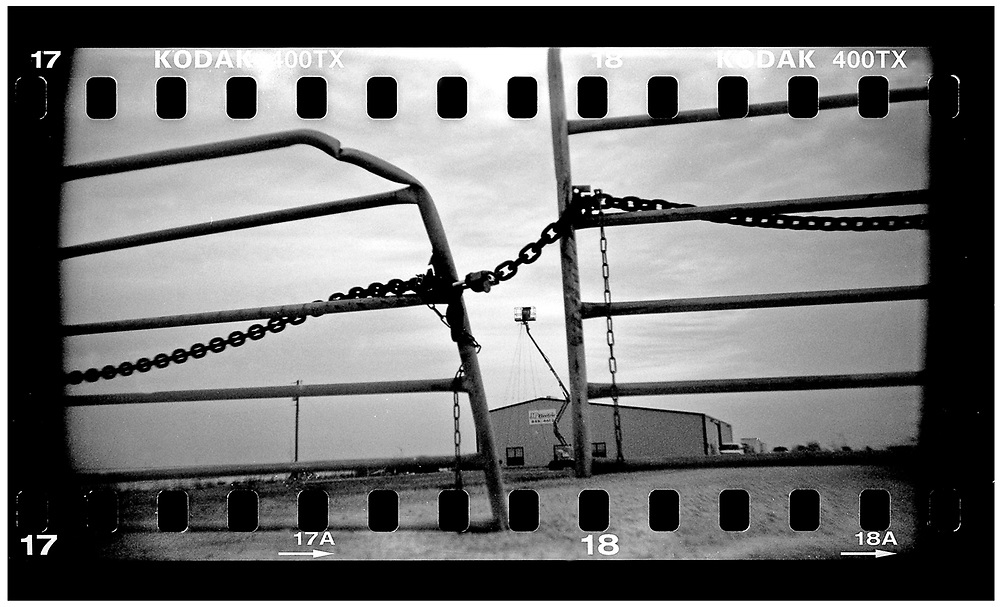 A gate is chained shut in Crawford, Texas, December 13, 2008. U.S. President George W. Bush moved to the small Texas town, population 705, in 1999 during his run for the presidency in 2000. The effect of the image was achieved by shooting 35mm black and white film in a medium format camera thereby exposing the entire negative including the sprocket holes of the film. REUTERS/Jim Young