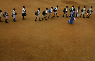 "Children follow their teacher as they head back to school, on the first day back to classes after the tsunami in the town of Panadura, Sri Lanka Monday Jan. 10, 2005.  Some 8,000 children will start lessons in makeshift school rooms _ some in tents pitched near their destroyed schools, some in buildings that did not fall and some using emergency ""school-in-a-box"" kits provided by UNICEF consisting of exercise books, pencils, chalk, teaching aids and some puzzles."