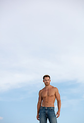 shirtless hunky man walking on a sand dune in White Sands, NM