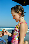 Young proudly displays a seashell found along the beach.