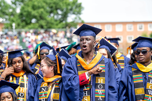 Graduating students in regalia cheering at Commencement.