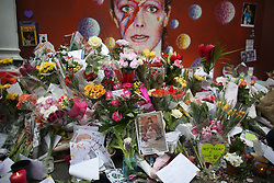 © Licensed to London News Pictures. 12/01/2016. London, UK. Tributes of flowers, cards and candles pile up in front of a mural of David Bowie in Brixton where he was born. Photo credit: Peter Macdiarmid/LNP
