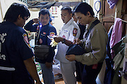 """Oct. 1, 2009 -- BANGKOK, THAILAND:  ORACHUN (center, white uniform) a medic with Poh Teck Tung and volunteers from Poh Teck Tung check the ID papers of a woman in Bangkok who attempted suicide. The 1,000 plus volunteers of the Poh Teck Tung Foundation are really Bangkok's first responders. Famous because they pick up the dead bodies after murders, traffic accidents, suicides and other unplanned, often violent deaths, they really do much more. Their medics respond to medical emergencies, from minor bumps and scrapes to major trauma. Their technicians respond to building collapses and traffic accidents with heavy equipment and the """"Jaws of Life"""" and their divers respond to accidents in the rivers and khlongs of Bangkok. The organization was founded by Chinese immigrants in Bangkok in 1909. Their efforts include a hospital, college tuition for the poor and tsunami relief.    Photo by Jack Kurtz / ZUMA Press"""