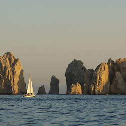 A classic sail boat on a sunset cruise near Land's End in Cabo San Lucas, Mexico.