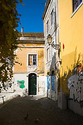 Graffiti and street art on brightly coloured wall of traditional architecture in Lisbon, Portugal