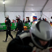 "Competitors prepare themselves in the Bobsleigh tent during the Bobsleigh Four-man competition  at The Whistler Sliding Centre, Whistler, during the Vancouver Winter Olympics. 26th February 2010. Photo Tim Clayton..'BOB'..Images from the Four-man Bobsleigh Competition. Winter Olympics, Vancouver 2010..History was made at the Whistler Sliding Centre when the USA four-man bobsleigh team, led by Steven Holcomb took the Gold. The first time since 1948, a gap of 62 years, since the USA have won an Olympic Bobsleigh gold and they did it with their sleigh named ""Night Train""...The four days of practice and competition show the tension, nervousness and preparation as the teams of hardened men cope with the challenge of traveling at average speeds of over 150 km an hour. Indeed, five teams had already pulled out of the event before the opening heats because of track complexity, speed and fear, and on the final day, another four teams did not start after six crashes in the first two heats...Teams warm up behind the start complex, warming muscles in the cold in preparation for the explosive start. Many teams prepare in silence, mentally preparing themselves as they wait at the top of the run, in the bobsleigh sheds and the loading areas for their turn. When it's time to slide each team performs it's own starting ritual, followed by the much practiced start out of the blocks for just over four seconds, the teams are then in the hands of the accomplished drivers as they hurtle down the track for just over fifty seconds...Spectators clamber for the best position on track to see the sleighs for a split second, many unsuccessfully try to capture the moments on camera, The rumble of the sleigh is heard then the crowds gasp as it hurtles past in a blur...The American foursome of  Steven Holcomb, Justin Olsen, Steve Mesler and Curtis Tomasevicz finished with a pooled four-heat time of 3min 24.46sec. The German team led by Andre Lange won the Silver Medal in a combined time of 3min 24."