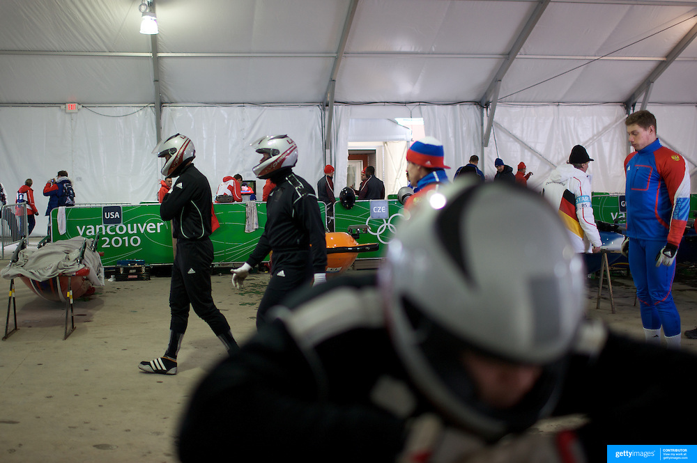 """Competitors prepare themselves in the Bobsleigh tent during the Bobsleigh Four-man competition  at The Whistler Sliding Centre, Whistler, during the Vancouver Winter Olympics. 26th February 2010. Photo Tim Clayton..'BOB'..Images from the Four-man Bobsleigh Competition. Winter Olympics, Vancouver 2010..History was made at the Whistler Sliding Centre when the USA four-man bobsleigh team, led by Steven Holcomb took the Gold. The first time since 1948, a gap of 62 years, since the USA have won an Olympic Bobsleigh gold and they did it with their sleigh named """"Night Train""""...The four days of practice and competition show the tension, nervousness and preparation as the teams of hardened men cope with the challenge of traveling at average speeds of over 150 km an hour. Indeed, five teams had already pulled out of the event before the opening heats because of track complexity, speed and fear, and on the final day, another four teams did not start after six crashes in the first two heats...Teams warm up behind the start complex, warming muscles in the cold in preparation for the explosive start. Many teams prepare in silence, mentally preparing themselves as they wait at the top of the run, in the bobsleigh sheds and the loading areas for their turn. When it's time to slide each team performs it's own starting ritual, followed by the much practiced start out of the blocks for just over four seconds, the teams are then in the hands of the accomplished drivers as they hurtle down the track for just over fifty seconds...Spectators clamber for the best position on track to see the sleighs for a split second, many unsuccessfully try to capture the moments on camera, The rumble of the sleigh is heard then the crowds gasp as it hurtles past in a blur...The American foursome of  Steven Holcomb, Justin Olsen, Steve Mesler and Curtis Tomasevicz finished with a pooled four-heat time of 3min 24.46sec. The German team led by Andre Lange won the Silver Medal in a combined time of 3min 24."""