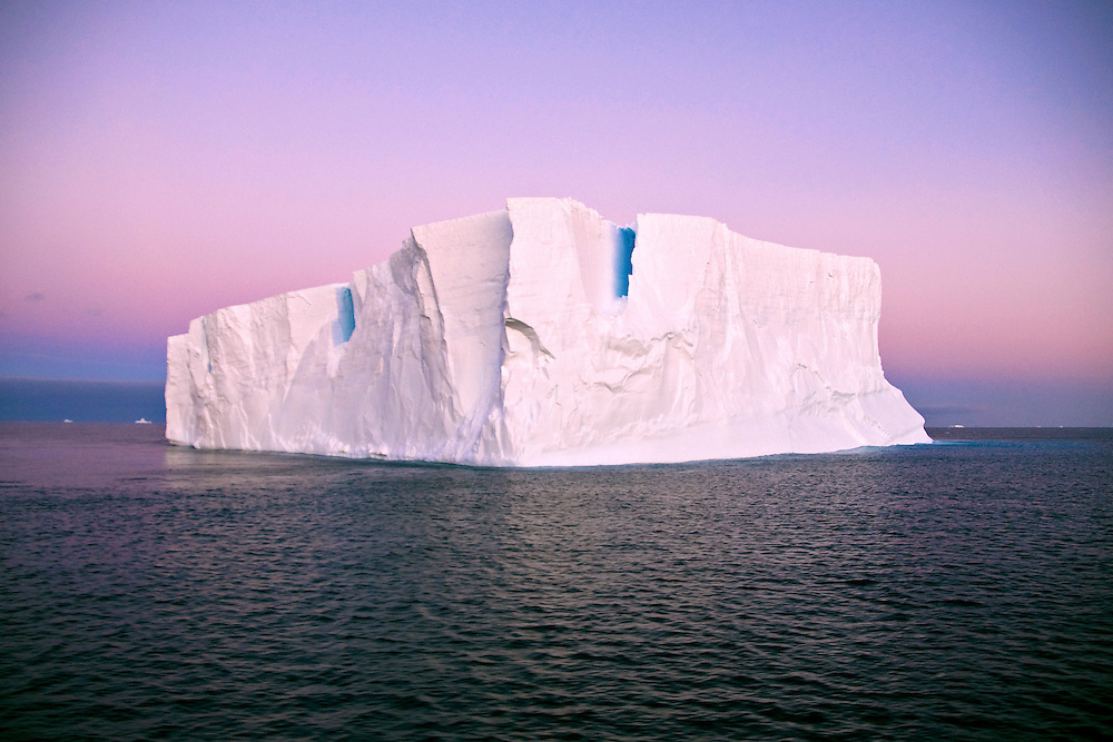 A large pure white iceberg floating off the shore of Antarctica.
