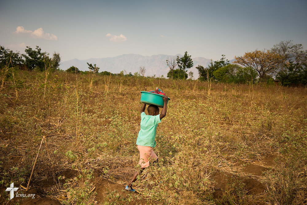 A young boy carries laundry from an LCMS funded borehole well over farmland on Sunday, Sept. 27, 2015, in Chingale, Malawi. LCMS Communications/Erik M. Lunsford
