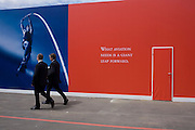 "Two businessmen pass-by a slogan about the future of the aviation industry written on a red hoarding at Britain's Farnborough Air Show, Hampshire, England. ""What aviation needs is a giant leap forward"" it says on a deep red background, next to a door that has also been covered in the primary colour. A pole vaulter is about to leap across the picture to prove the giant momentum needed to spring aviation into the future. The Air Show is one of Europe's premier aviation show events, attracting global companies selling aerospace equipment and enthusiasts who watch daily flying displays. It is seen as a thermometer for current innovation and future trends."