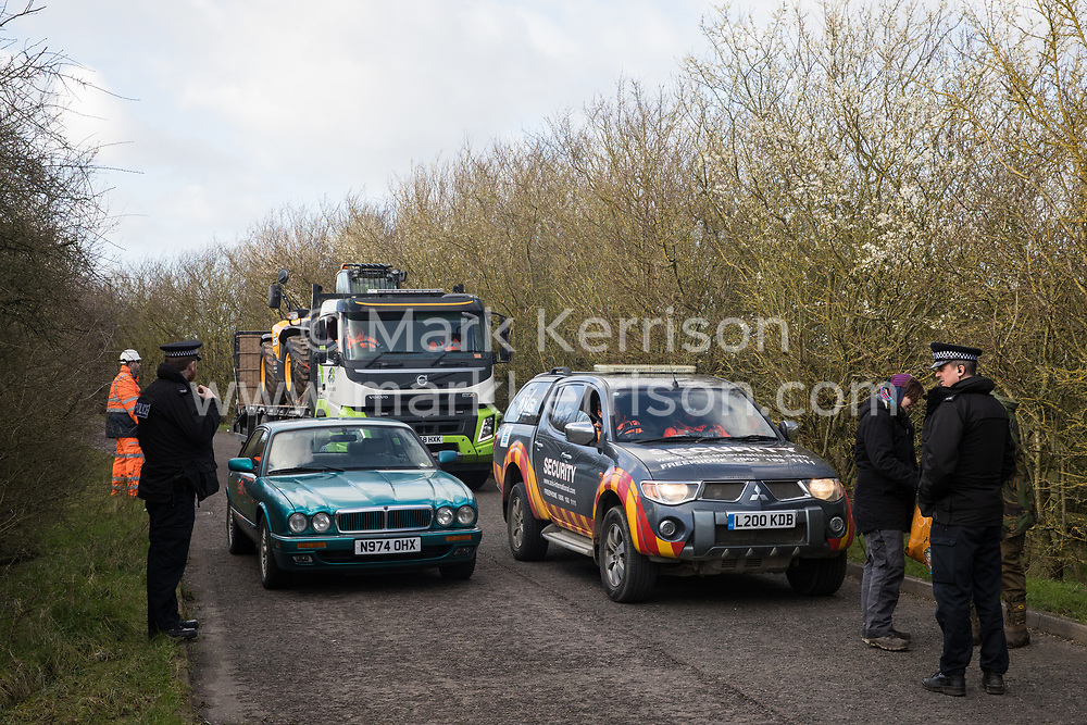 Denham, UK. 11 February, 2020. Environmental activists from Extinction Rebellion, Stop HS2 and Save the Colne Valley pick up litter as they 'slow walk' in front of a large truck transporting a JCB forklift truck to a HS2 site at Denham in the Colne Valley. Local traffic passes on the other side of the road. Contractors working on behalf of HS2 are rerouting electricity pylons through a Site of Metropolitan Importance for Nature Conservation (SMI) in conjunction with the high-speed rail link.