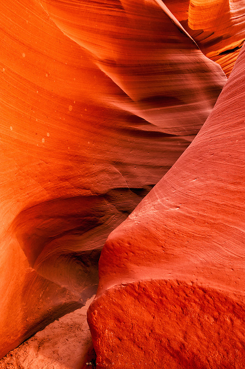 Lower Antelope Canyon, AZ<br /> RP1868012.<br /> Sadly, the Antelope slots have become such icons that they are more an exercise in frustration than a destination.  In 1997 when I first went, there were 2 trucks at Upper; they dropped you off, and if you wanted to stay longer you came back on a later truck.  There were no guides, unless you got a guided trip from Page.  In awe, I felt I was in a special, sacred place.  Few people were there, hardly anyone spoke above a whisper, walking slowly, afraid to disturb the ambience. The incredible striations of the walls, dust particles floated here and there, sometimes being caught and becoming a mote of bright light like a firefly.   No one would have dreamed of defacing this beautiful sandstone by making a tag or carving their name.   I was fortunate to go a few times over the years, and came to love it in there, and even though they are not that big, I never tired of it.<br /> Well, that's all changed.  I counted 8 trucks at Upper, and so many guided trips, even from Flagstaff and Sedona, coming in, there couldn't possibly be time in those narrow chambers to get a good composition.  Guides were now required.  Time limits strictly enforced.  They didn't even want you to bring in a tripod.<br /> I retreated in disgust to Lower Antelope Canyon, where a photographer can still enter unguided.  Of course, it costs more, and you pay for extra time spent.  And extra time you WILL spend, as the guided groups come through right on top of one another.  I spent more time pressed against the wall as body after body passed, getting my exposure set and hoping I'd have time to compose and still do the long exposures before the next group.  The sacredness is gone.  People have left their names on walls.  There is incessant chatter, singing, even flutes and guitars brought in by guides.  There's not much time to appreciate the Wonder of these slots, nor do people apparently want you to--you are just holding them up on the way to the other end.  I understand the