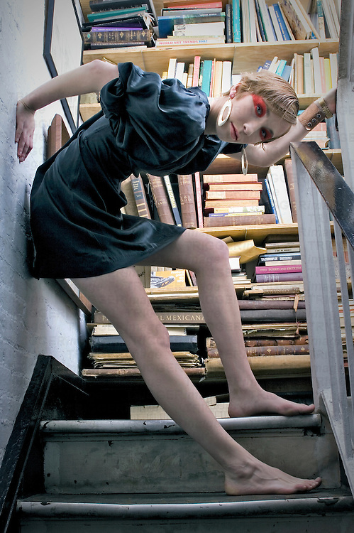 A young woman standing on stairs infront of a bookshelf