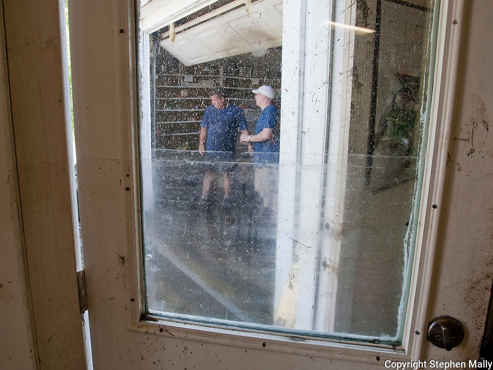 The waterline can be seen on a door as workers clean out Hartwick Marina in Delhi, Iowa on Monday, July 26, 2010.
