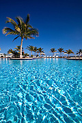 Water reflections on clear blue swimming pool surrounded by palm trees