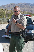 Policeman using walkie talkie near police car