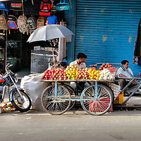 Apples and Oranges on Bicycle Cart in Port Blair, India<br /> Street vendors in Port Blair, India, seem to have two things in common.  Their business is on wheels like this vendor of apples and oranges who sells from a cart with bicycle tires.  They also have attached an umbrella to help shield from the excessive heat that averages from 84 to 90 degrees Fahrenheit year round.
