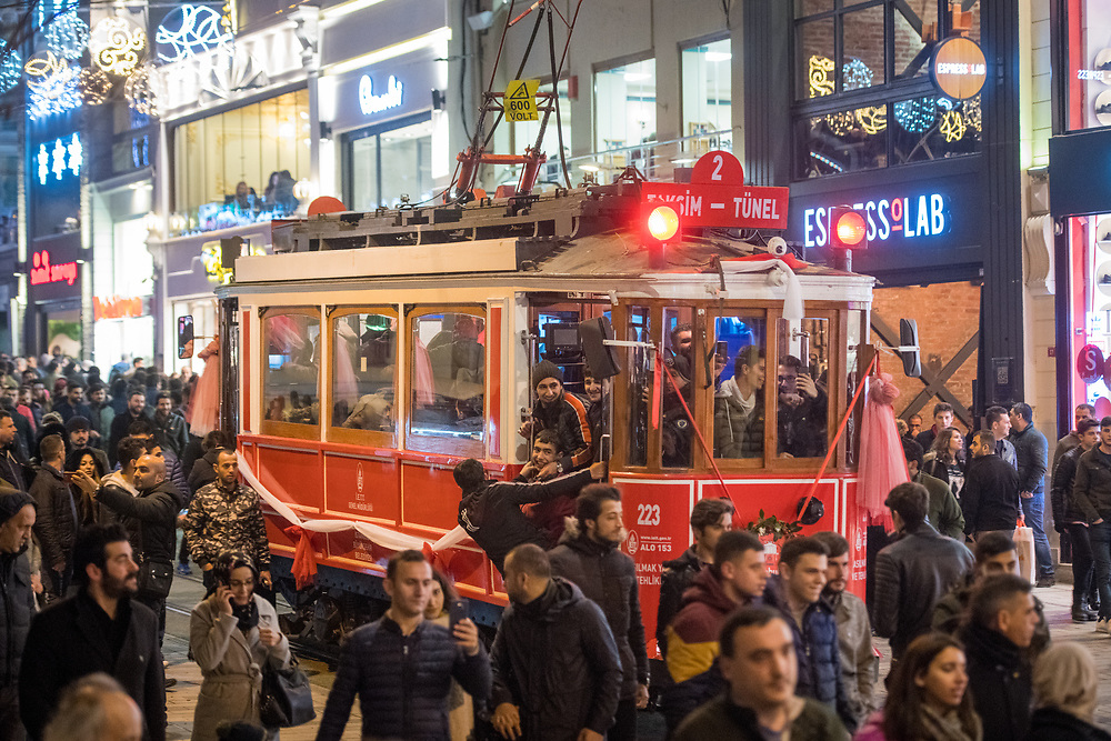 Passengers grip onto the sides of trolley car as it makes it way through the crowded streets of Istanbul, Turkey